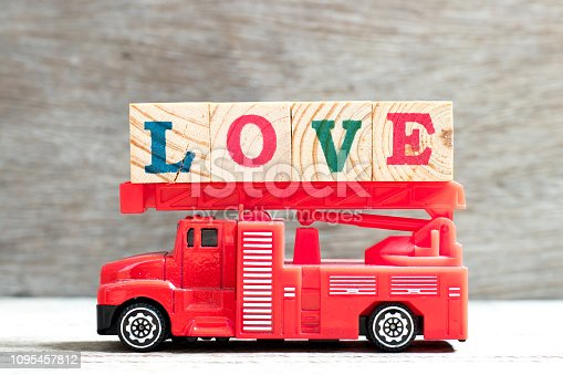istock Toy fire ladder truck hold letter block in word love on wood background 1095457812
