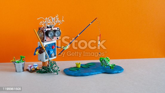 istock Toy fisherman caught big fish. Robotic fishing vacation concept. Funny angler with accessories rod bucket bait. Blue lake on orange background, copy space 1199961505