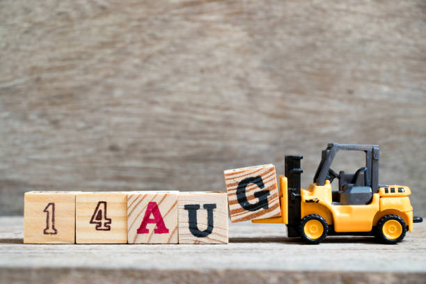 Toy forklift hold block G to complete word 14 aug on wood background (Concept for calendar date in month August) stock photo