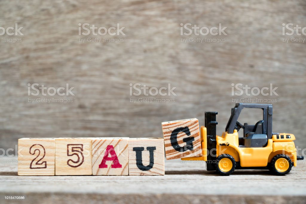 Toy forklift hold block G to complete word 25 aug on wood background (Concept for calendar date in month August) stock photo