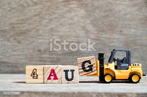 istock Toy forklift hold block G to complete word 4 aug on wood background (Concept for calendar date in month August) 1010725982