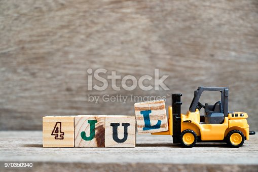 istock Toy forklift hold block l to complete word 4 jul on wood background (Concept for calendar date in month July) 970350940