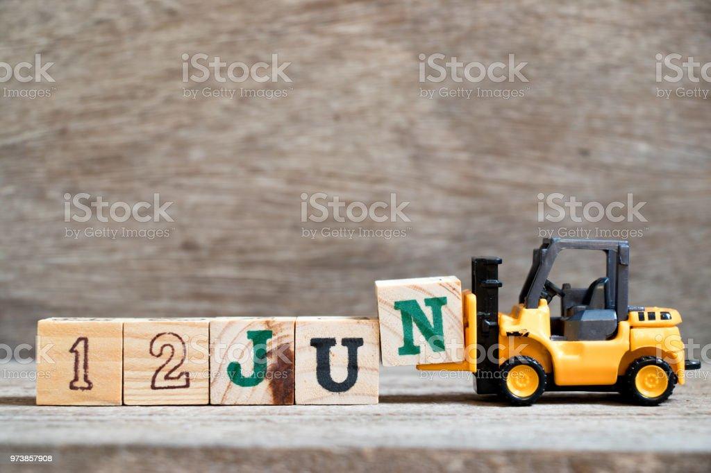 Preensão de empilhadeira brinquedo bloco N para completar a palavra 12 jun sobre fundo madeira (conceito de data do calendário no mês de junho) - foto de acervo