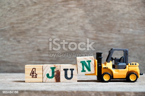 istock Toy forklift hold block N to complete word 4 jun on wood background (Concept for calendar date in month June) 955484186