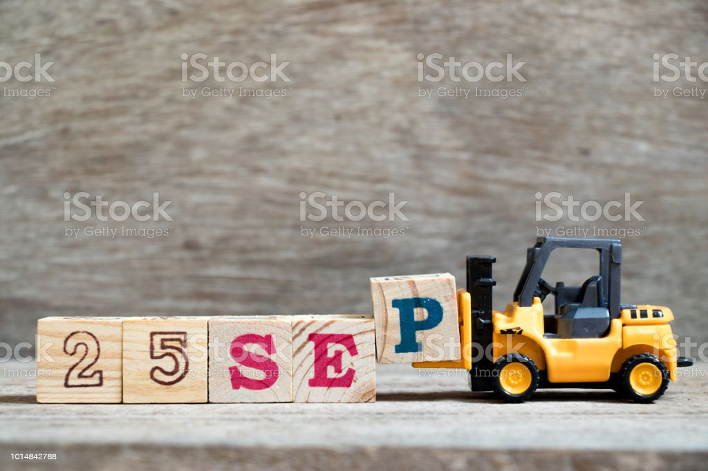 Toy forklift hold block P to complete word 25 sep on wood background (Concept for calendar date in month September) stock photo