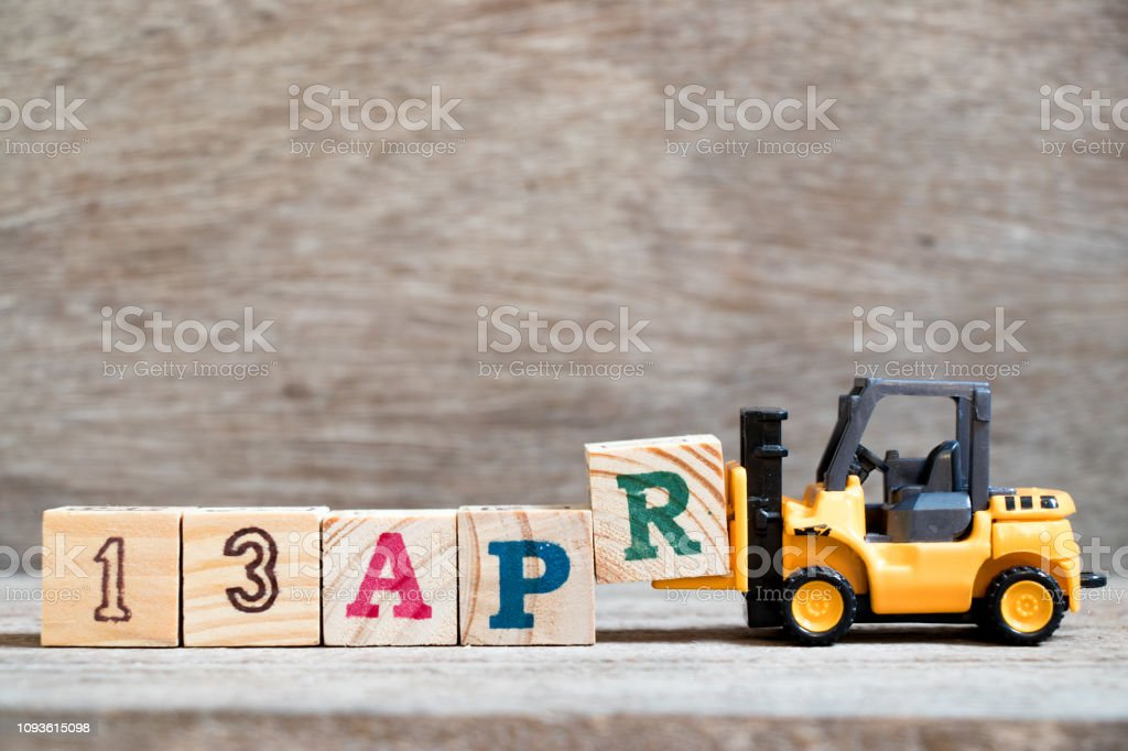 Toy forklift hold block R to complete word 13apr on wood background (Concept for calendar date 13 in month april) stock photo