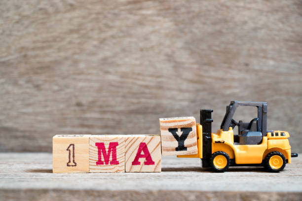 Toy forklift hold block Y to complete word 1may on wood background (Concept for calendar date 1 for month May) stock photo