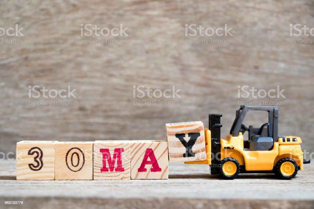 Leksak gaffeltruck Håll block Y till komplett word 30 kan på trä bakgrund (koncept för kalenderdatum för månaden maj) - Royaltyfri Affisch Bildbanksbilder