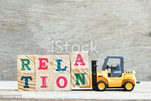 Toy forklift hold letter block a, n to complete word relation on wood background