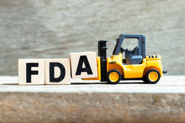 toy forklift hold letter block a to complete word fda (abbreviation of food and drug administration) on wood background - fda stock photos and pictures