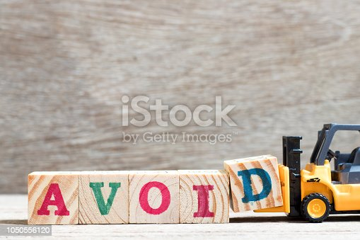 Toy forklift hold letter block d to complete word avoid on wood background