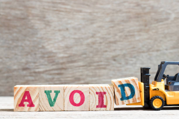 Toy forklift hold letter block d to complete word avoid on wood background Toy forklift hold letter block d to complete word avoid on wood background avoidance stock pictures, royalty-free photos & images