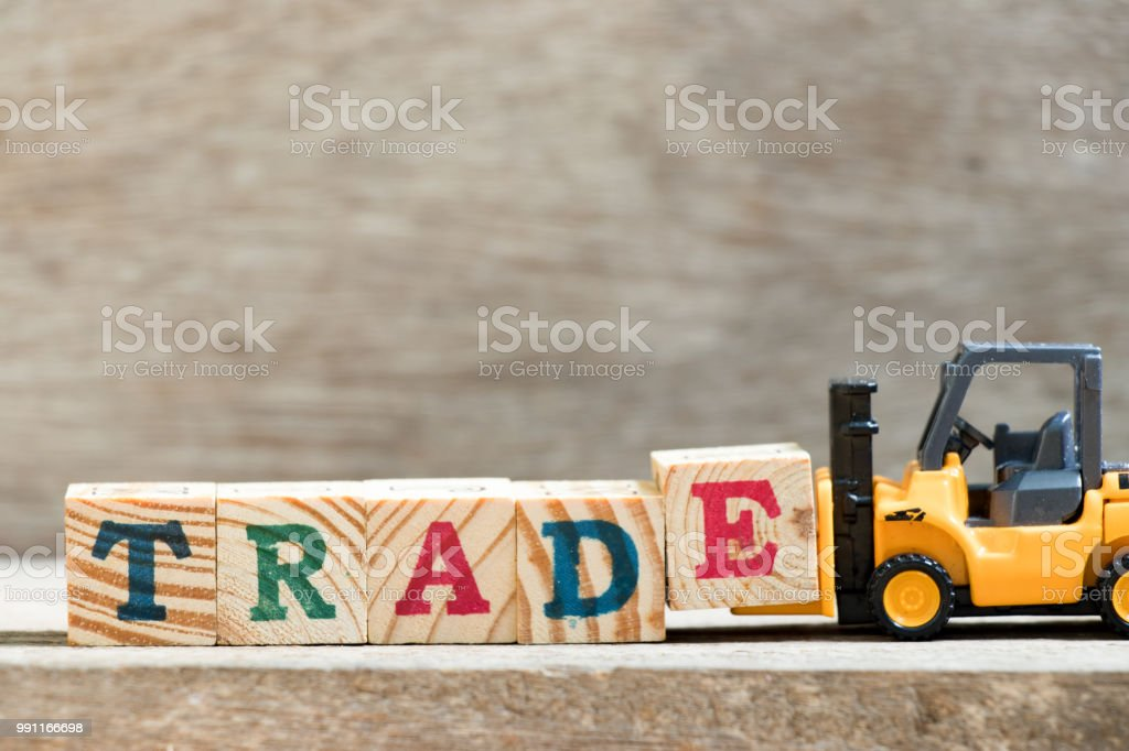 Toy forklift hold letter block E in word trade on wood background stock photo