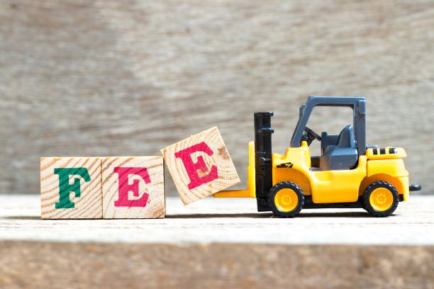 Toy forklift hold letter block e to complete word fee on wood background Toy forklift hold letter block e to complete word fee on wood background fee stock pictures, royalty-free photos & images