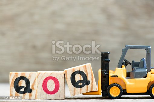 istock Toy forklift hold letter block  in word qoq (abbreviation of quarter on quarter) on wood background 1081500870