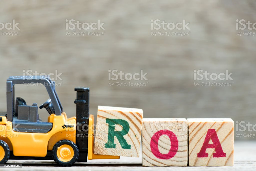 Toy forklift hold letter block  in word ROA (abbreviation of return on assets) on wood background stock photo