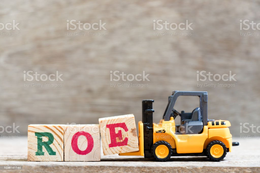 Toy forklift hold letter block  in word ROE (abbreviation of return on equity) on wood background stock photo