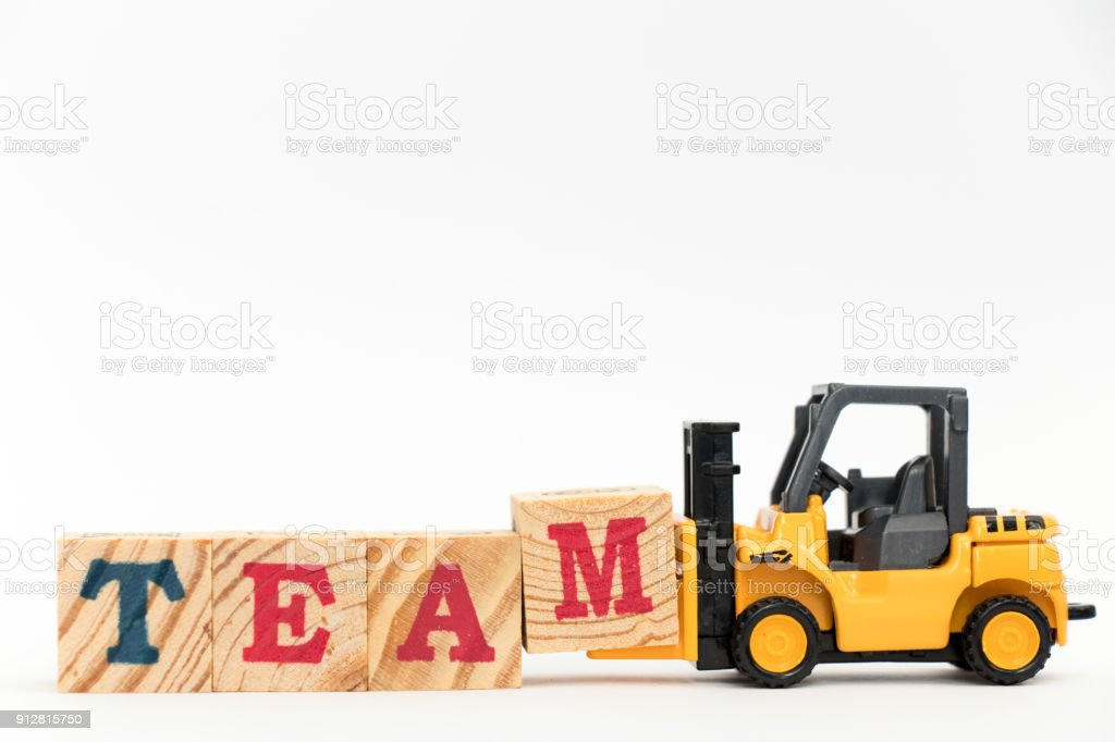 Toy forklift hold letter block M to complete word on team white background stock photo