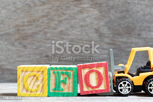 istock Toy forklift hold letter block O to complete word CFO (Abbreviation of Chief Financial Officer) on wood background 1161201723