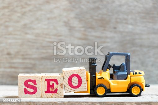 1045434476istockphoto Toy forklift hold letter block O to complete word SEO (abbreviation of Search Engine Optimization) on wood background 959633374