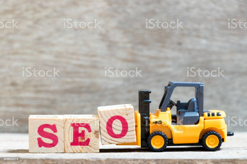 Toy forklift hold letter block O to complete word SEO (abbreviation of Search Engine Optimization) on wood background – zdjęcie