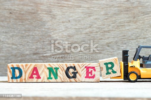 istock Toy forklift hold letter block R to complete word danger on wood background 1144087285