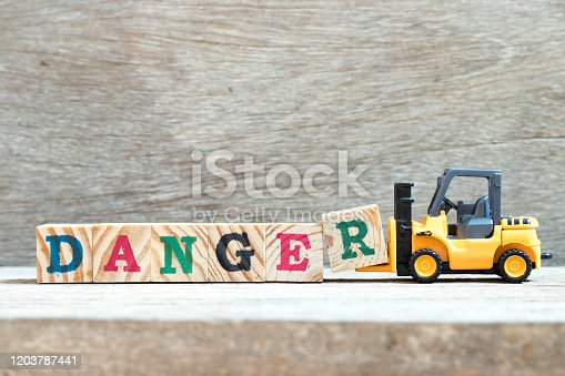 istock Toy forklift hold letter block R to complete word danger on wood background 1203787441