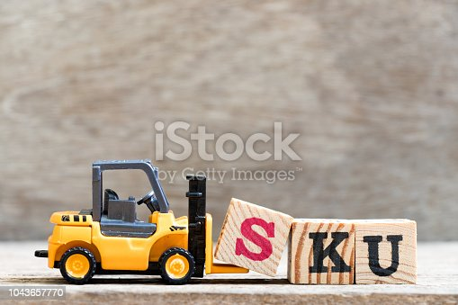istock Toy forklift hold letter block S in word SKU (abbreviation of stock keeping unit) on wood background 1043657770