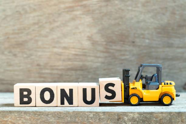 toy forklift hold letter block s to complete word bonus on wood background - bonus foto e immagini stock