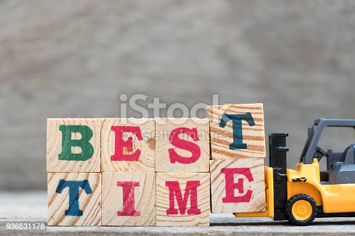 istock Toy forklift hold letter block T and E to complete word best time on wood background 936531178