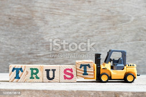 939533958 istock photo Toy forklift hold letter block t to complete word trust on wood background 1033823818
