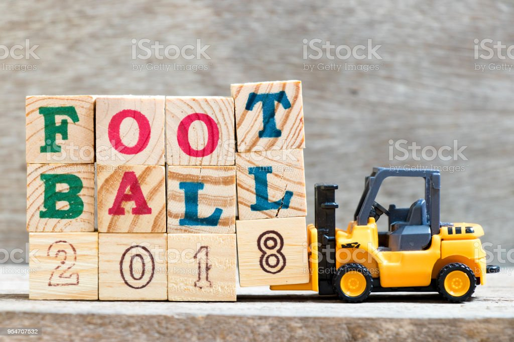 Toy forklift hold letter block T,L,8 to complete word  football 2018 on wood background stock photo