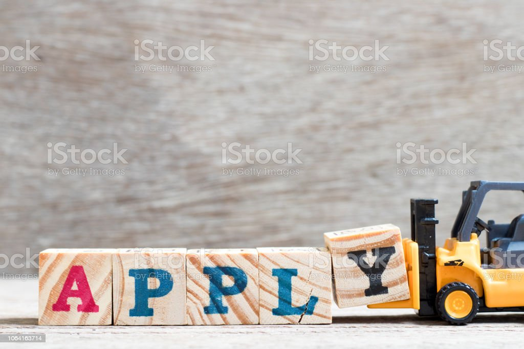Toy forklift hold letter block y to complete word apply on wood background stock photo