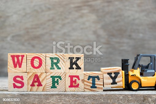 istock Toy forklift hold letter block Y to complete word work safety on wood background 905632830