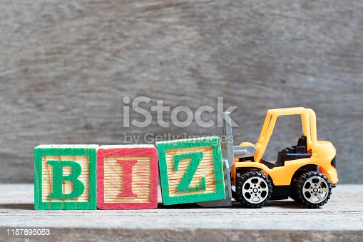 Toy forklift hold letter block Z to complete word biz (Abbreviation of business) on wood background