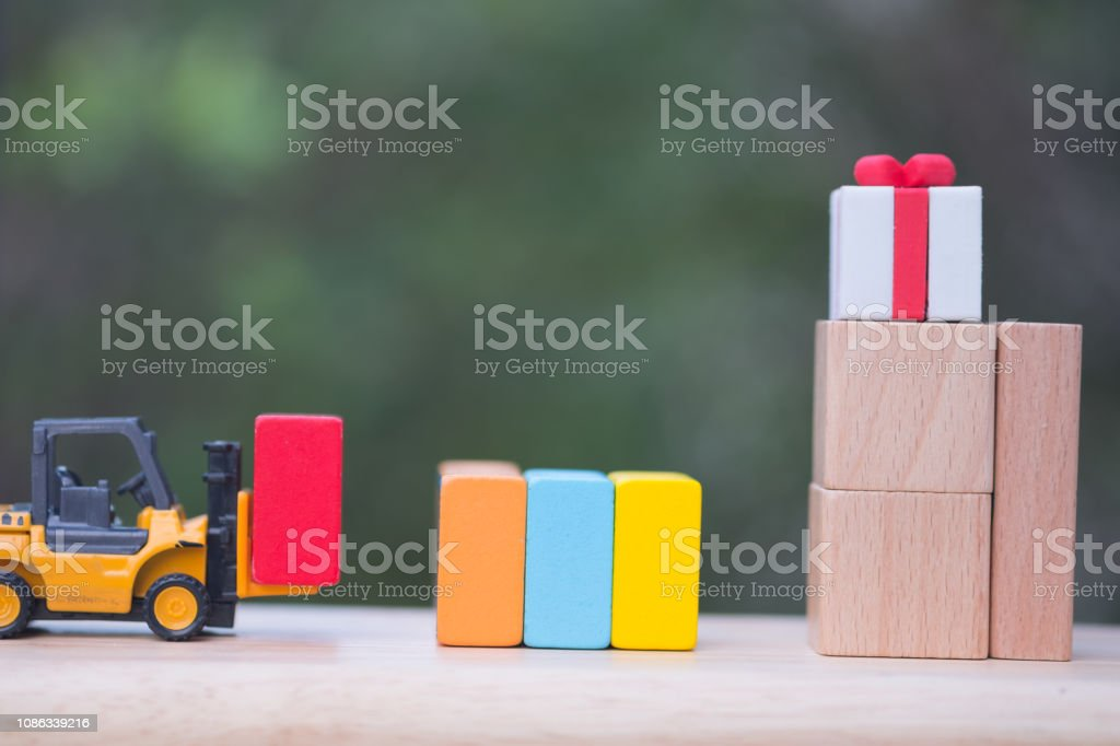 A toy forklift truck delivering of gift box. Gift delivery concept