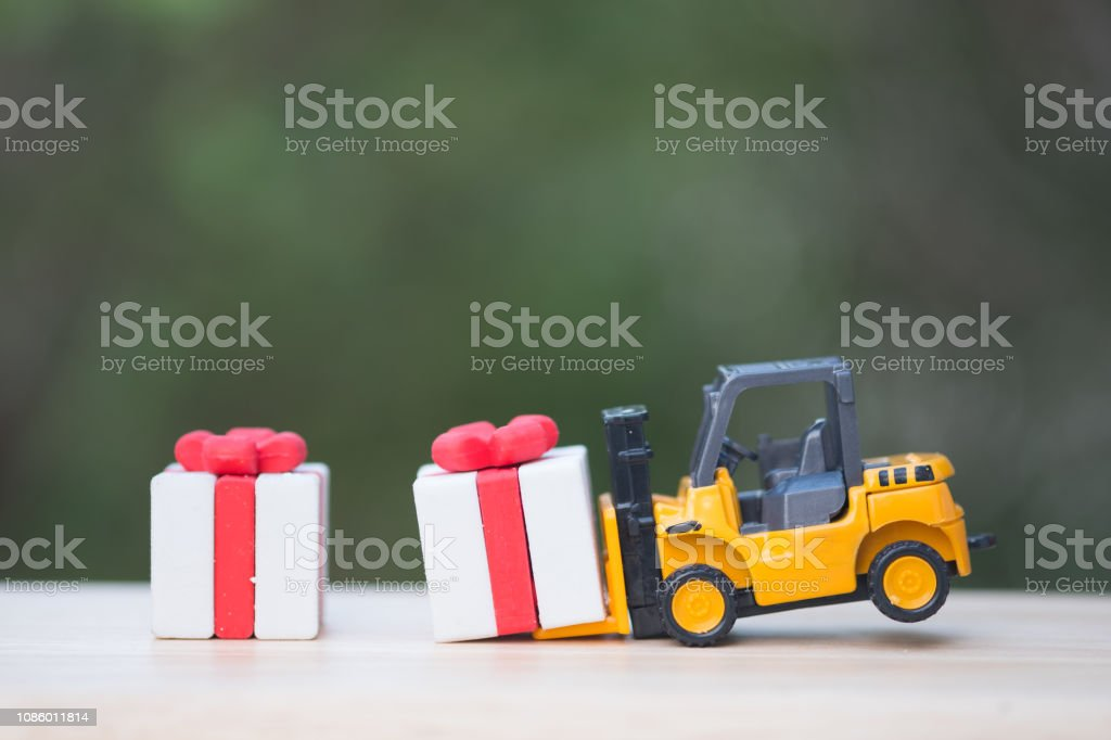 Toy forklift truck with Christmas gift box. Delivering presents...