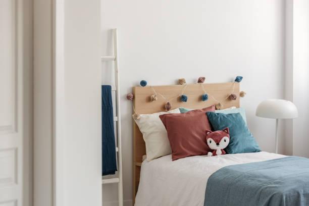 spielzeug fuchs und blau und ingwer kissen auf einzelbett in weißen schlafzimmer interieur für kinder - fuchs kissen stock-fotos und bilder