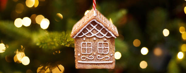 Toy gingerbread house hanging on the Christmas tree, holiday decor stock photo