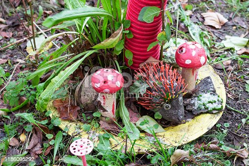 toy hedgehog with mushrooms in the garden. decorations for winter backyard