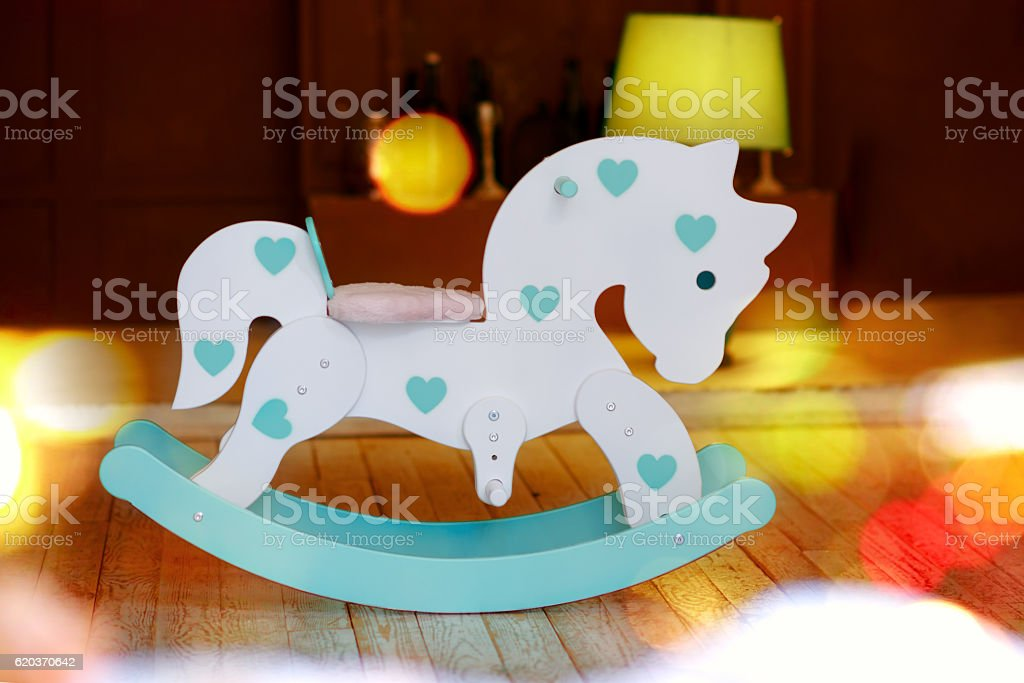 Toy horse with christmas lights on wooden background zbiór zdjęć royalty-free