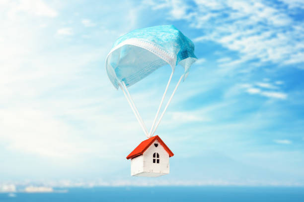 A toy house flies on a parachute from a medical mask. The concept of a protected house from viruses A toy house flies on a parachute from a medical mask. The concept of a protected house from viruses quarantine stock pictures, royalty-free photos & images