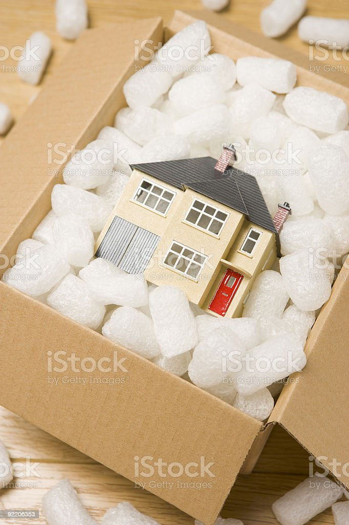 Toy house in a moving box with packing peanuts royalty-free stock photo