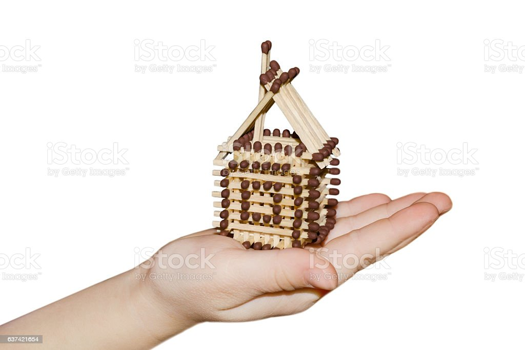 Toy house in hand isolated on white background stock photo
