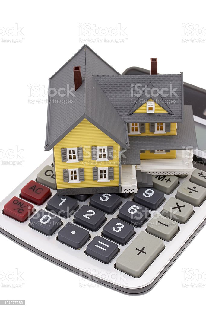 A toy house on top of a large calculator stock photo