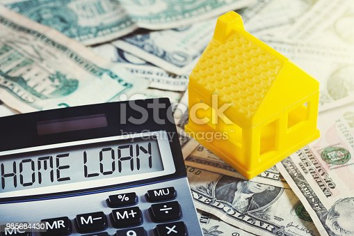 NOTE: The plastic house is an unbranded, generic toy. A little yellow toy house sitting on stacks of dollars symbolizes home financing as well as domestic finances. A calculator marked HOME LOAN  sits alongside.