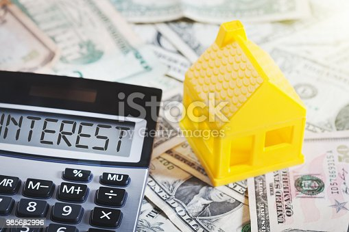 NOTE: The plastic house is an unbranded, generic toy. A little yellow toy house sitting on stacks of dollars symbolizes home financing as well as domestic finances. A calculator marked INTEREST sits alongside.