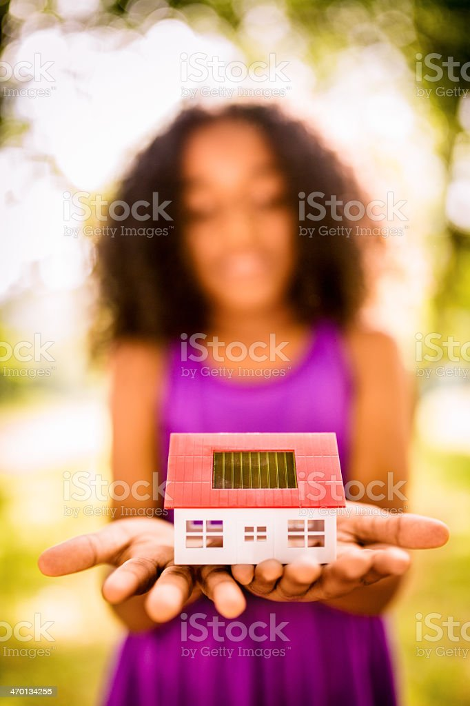 Close up of a toy house with a solar cell on it\'s roof being held by...