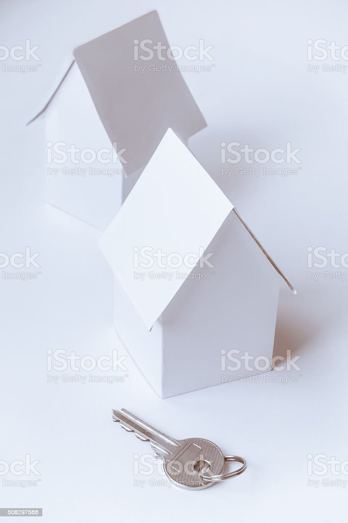 Toy houses and a key on white background stock photo