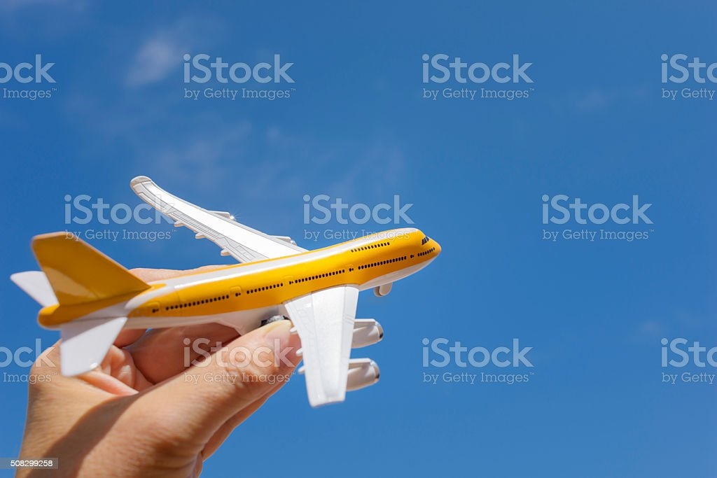 Toy Jet Airliner in Hand Against Blue Sky stock photo
